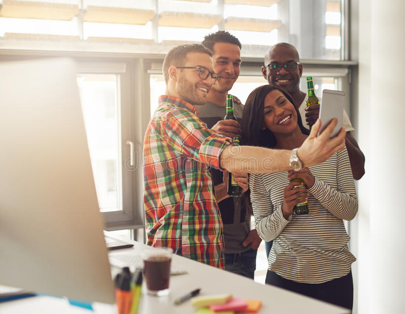 Four workers taking pictures with phone. Diverse group of four happy young workers celebrating with beer and taking pictures with camera phone near desk with stock photo