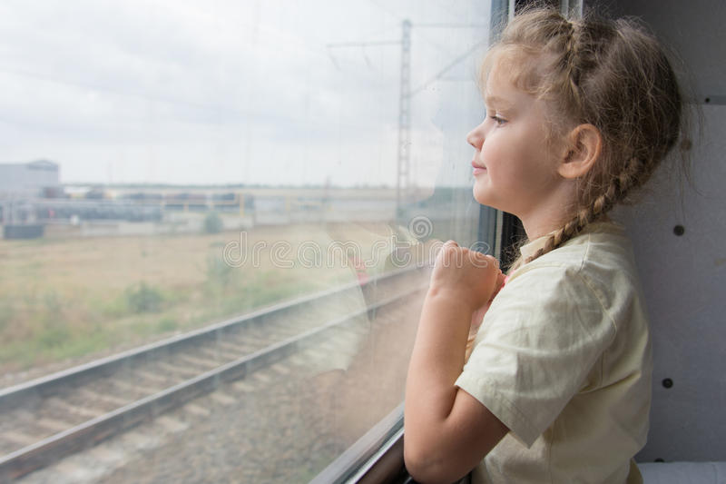 Four-year girl looks out the window of the train car stock photo