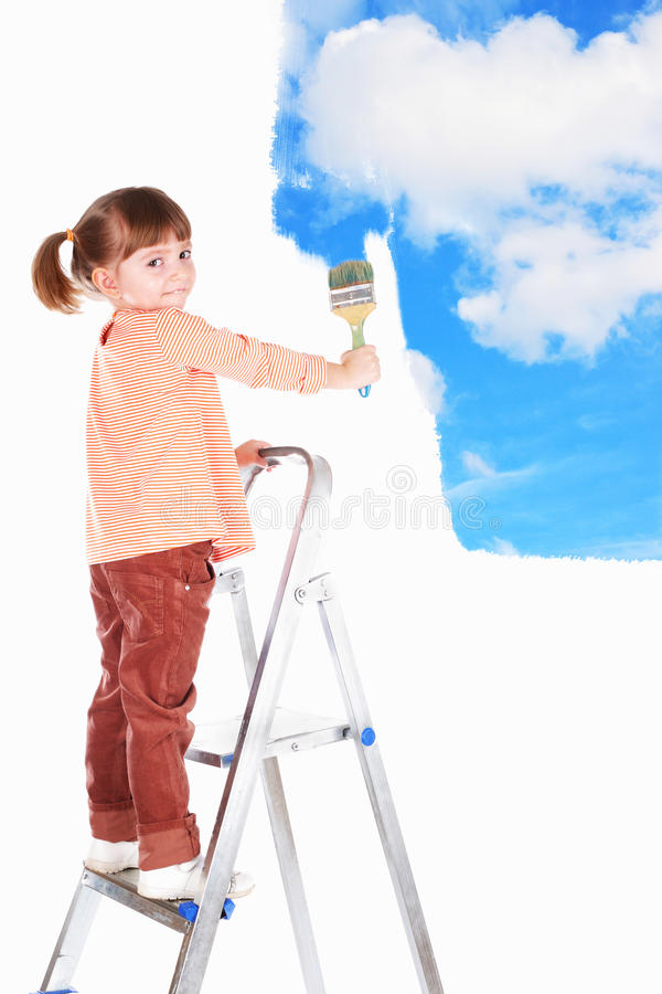 Four-year girl stand on a ladder and draws a pictu stock images