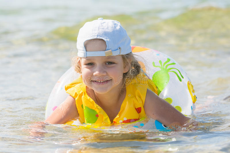 Four-year girl swims in the summer with a circle in the sea. Four-year girl swims in the summer with a lifeline and vest in the sea stock photography