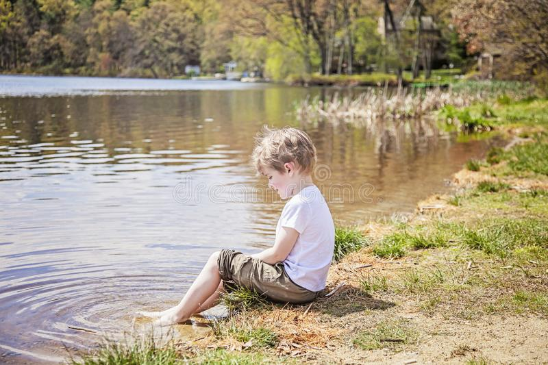 Boy sitting on shore of lake stock images