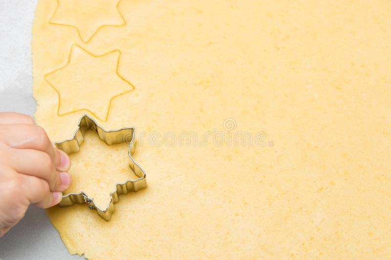 Four year old caucasian boy cutting from rolled out shortbread dough cookies with cutter on kitchen table. Top view copy space stock photos