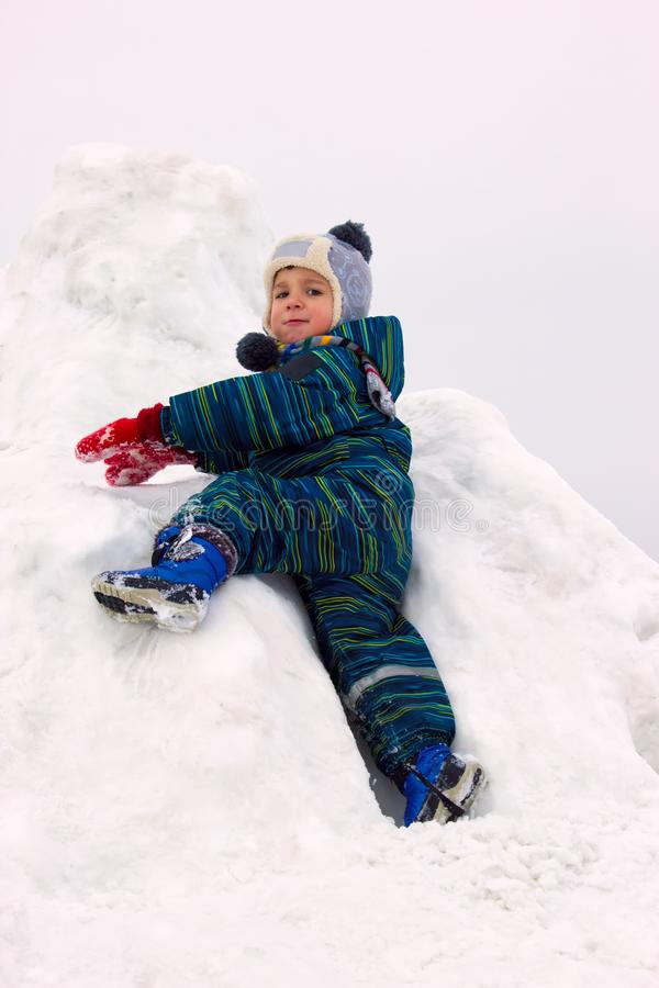 A four-year-old child, a boy, climbs a snowy hill royalty free stock image