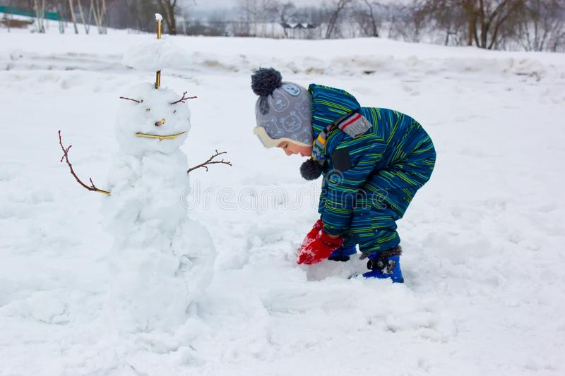 A four-year-old child, a boy, sculpts a snowman royalty free stock photography
