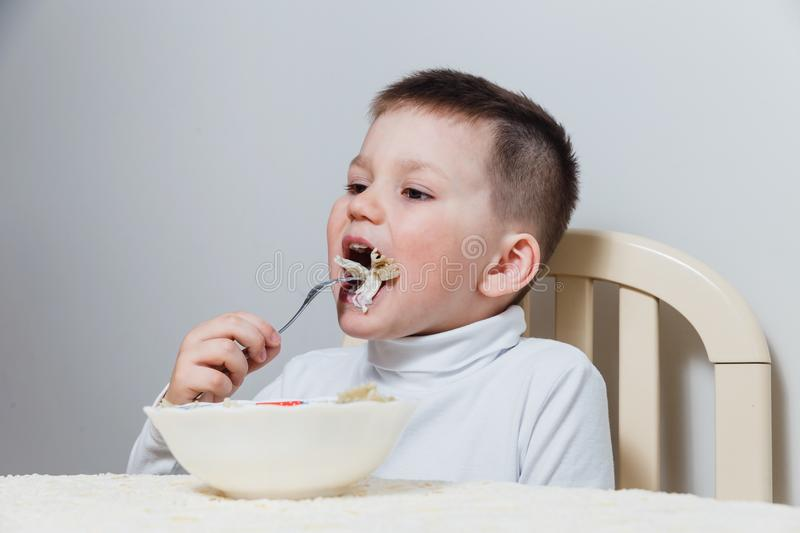 Four-year-old child in a white turtleneck eating pasta with a fork at the table stock photography