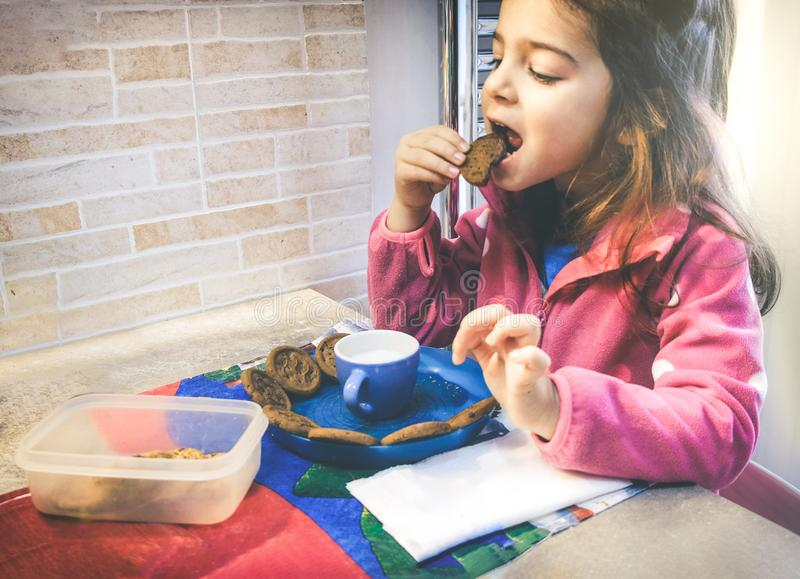 Four-year-old girl has breakfast with milk and biscuits in the kitchenette at home stock photos