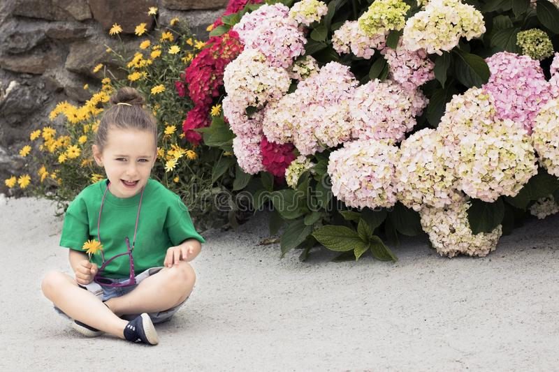 A four-year-old girl holds a marigold flower. A four-year-old girl, dressed in a green shirt, wearing purple glasses and sitting on the ground in front of stock photos