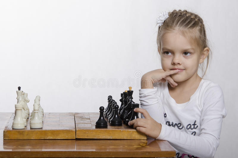 Download Four-year-old Girl With A Sly Look, Plays Chess Stock Photo - Image: 35786252
