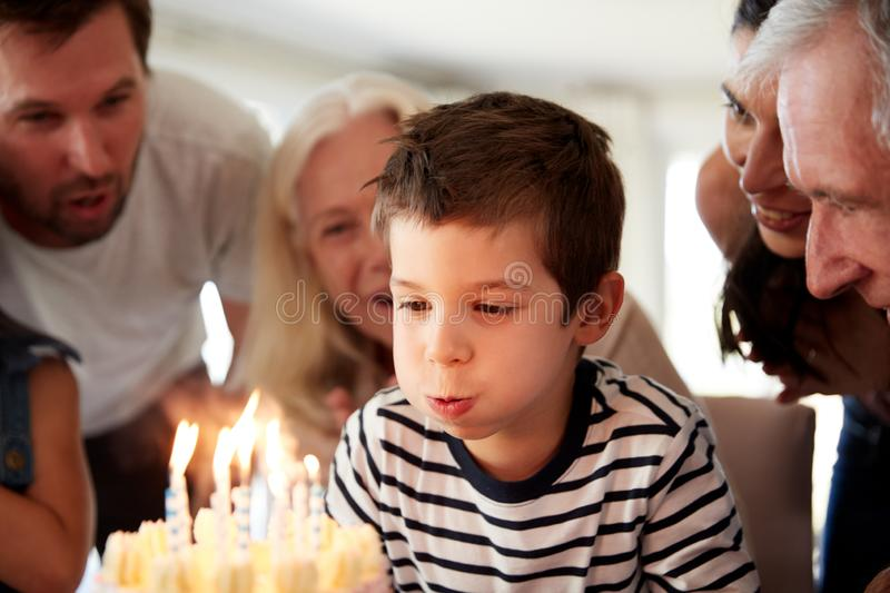 Four year old white boy celebrating with family blowing out candles on his birthday cake, close up royalty free stock photography