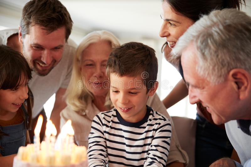 Four year old white boy and his family celebrating his birthday with cake and lit candles, close up stock photography