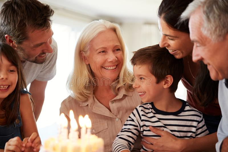 Four year old white boy and his family celebrating with a birthday cake and lit candles, close up royalty free stock photos