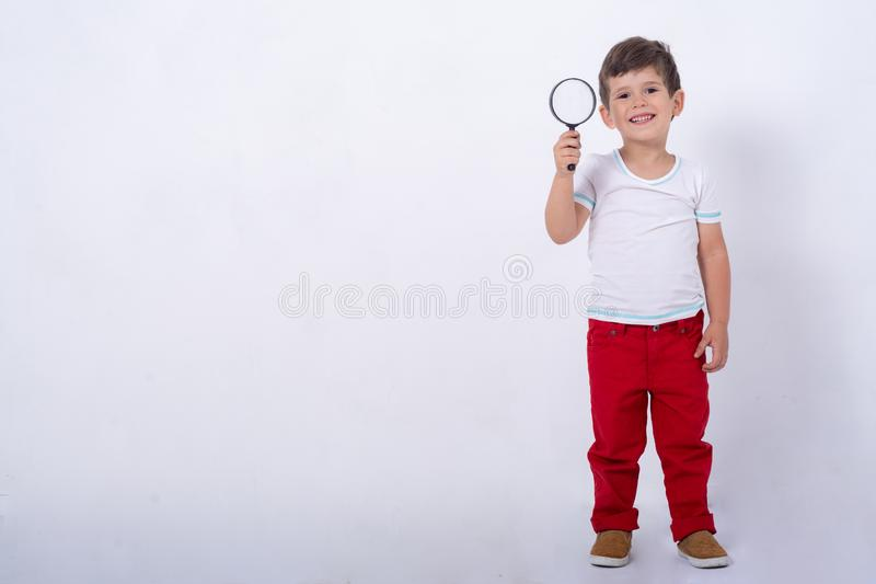 Four years boy looking through a magnifying glass, preschool kids, education. Isolated on white background, modern learning kids. Copy space for text stock image