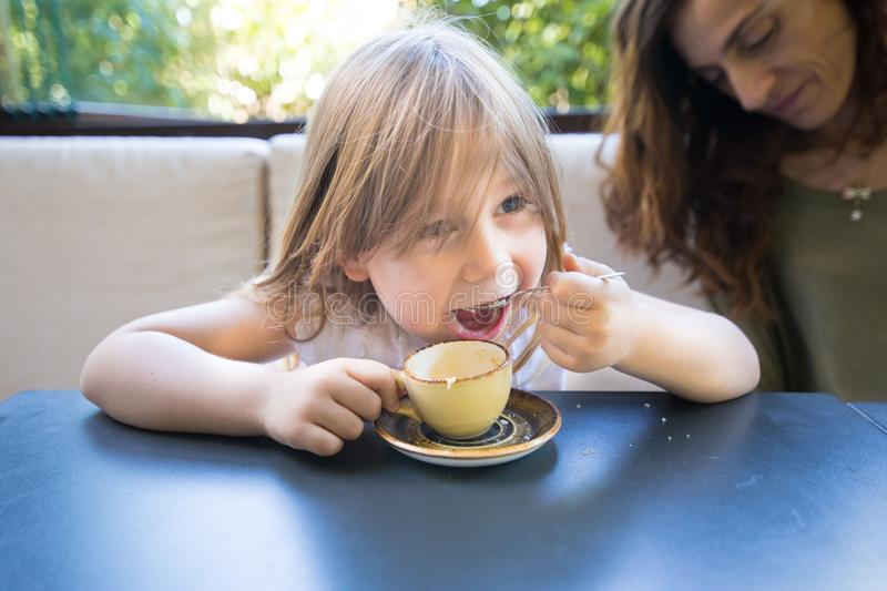 Little child eating sugar with spoon from coffee cup stock image
