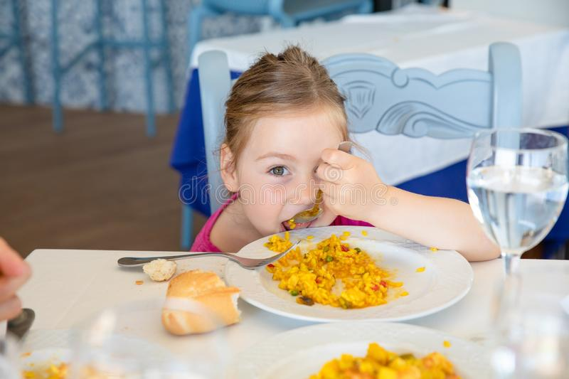 Funny little girl eating paella and looking at you. Four years old blonde girl eating Spanish paella rice with spoon from white plate, sitting in restaurant royalty free stock photography