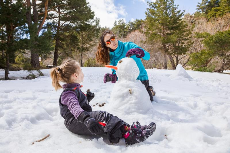Mother and little girl making a snowman in nature royalty free stock photo