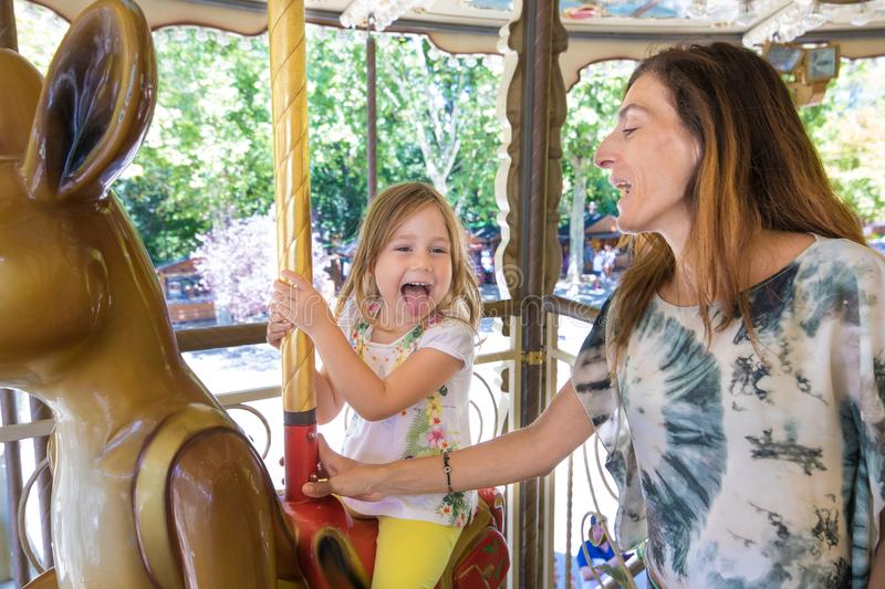 Little girl in carousel with mother sticking her tongue out. Four years old blonde happy girl sitting or riding and enjoying on an animal in a carousel, next to stock images