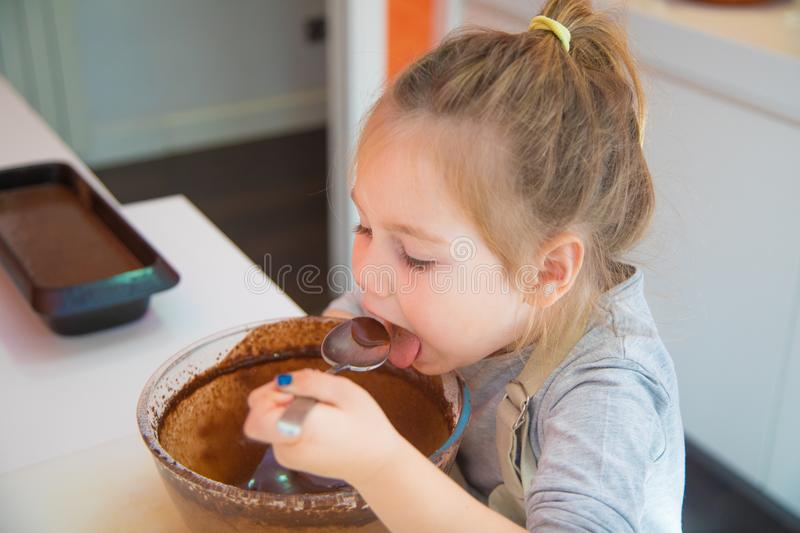 Girl tasting whipped chocolate cream from glass bowl with spoon stock image