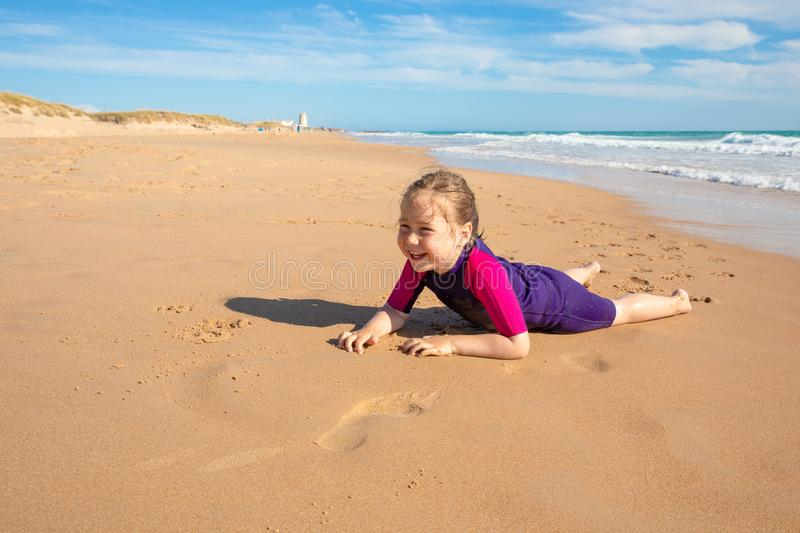 Surfer little girl lying on sand of beach laughing stock photography