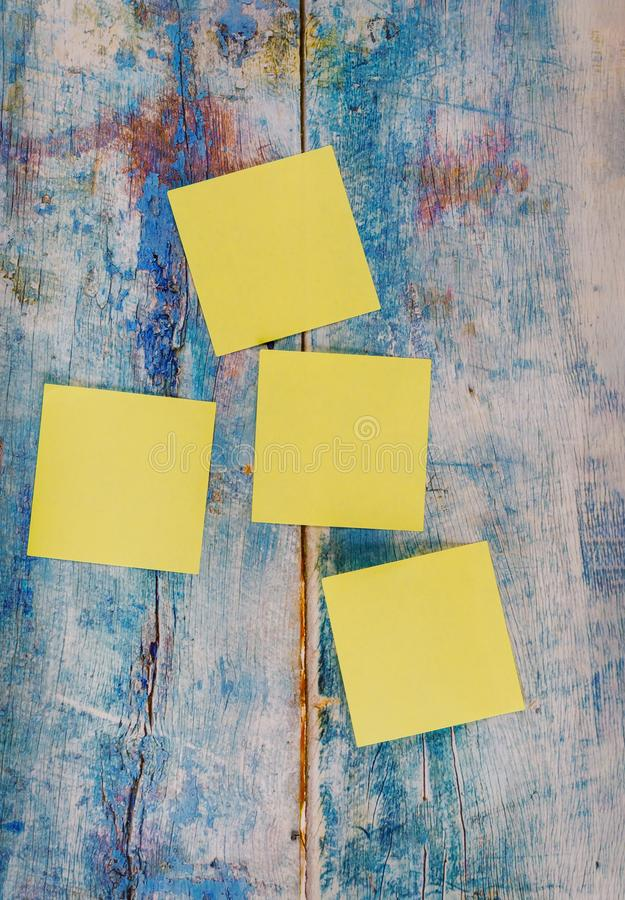 Four yellow empty square stickers in the blue old wooden background. Four empty square yellow stickers in the blue old wooden background, paper, note, sticky stock images