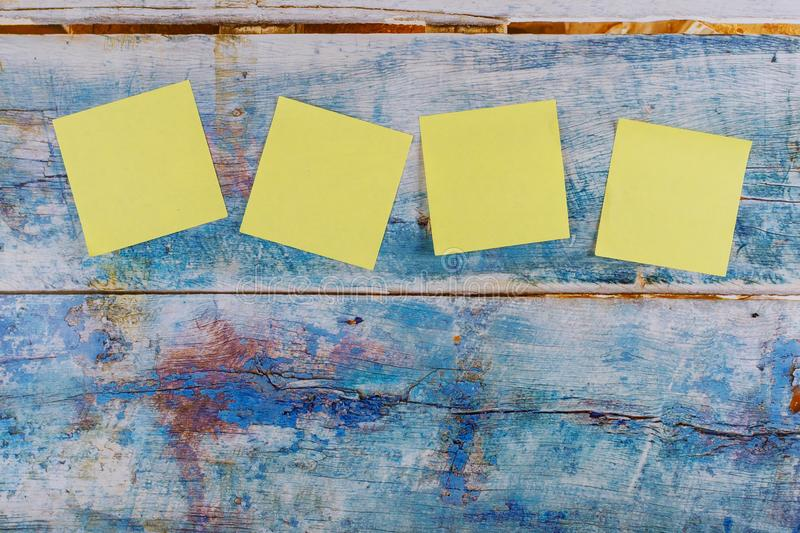 Yellow four sticker note in the blue old wooden background. Four yellow sticker note in the blue old wooden background, paper, sticky, blank, business, reminder royalty free stock photos