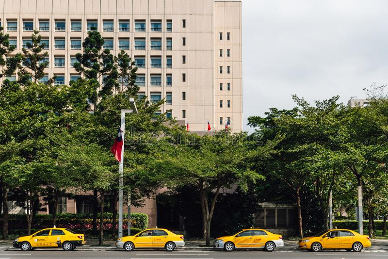 Four yellow taxis waiting for customers along the street that near the park with trees and building in the background in Taipei. royalty free stock photos