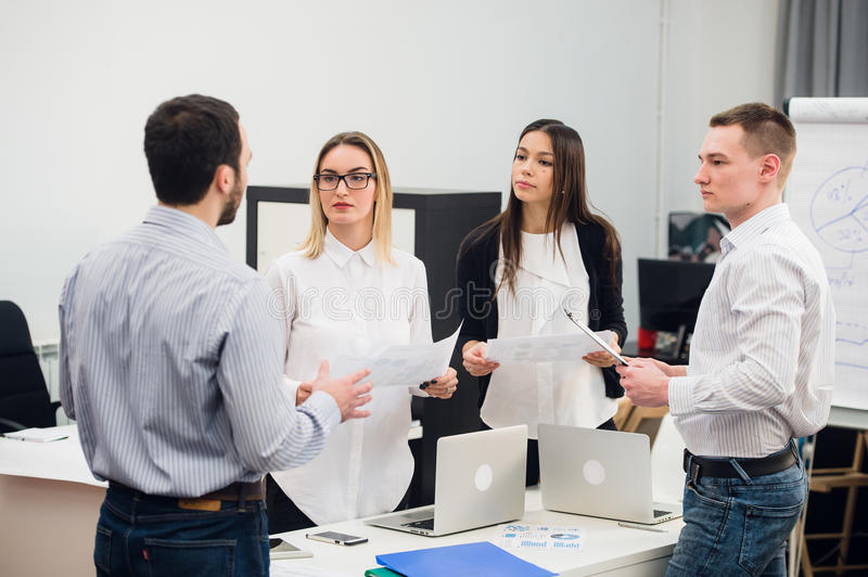 Four young business people working as a team gathered around laptop computer in an open plan modern office royalty free stock photo