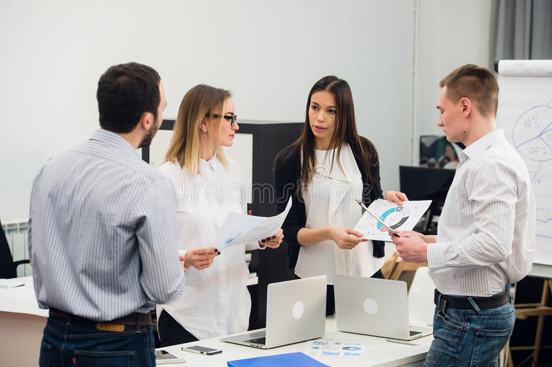 Four young business people working as a team gathered around laptop computer in an open plan modern office royalty free stock image