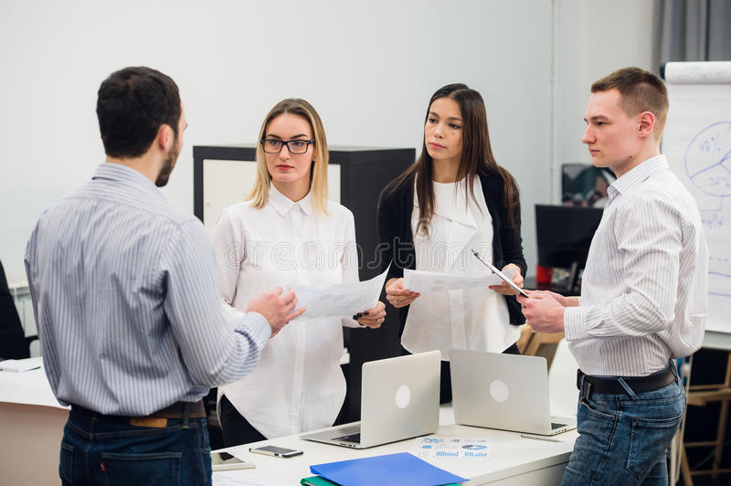 Four young business people working as a team gathered around laptop computer in an open plan modern office stock image