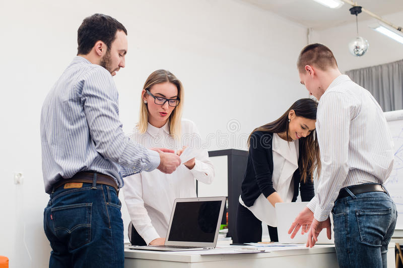 Four young business people working as a team gathered around laptop computer in an open plan modern office royalty free stock images