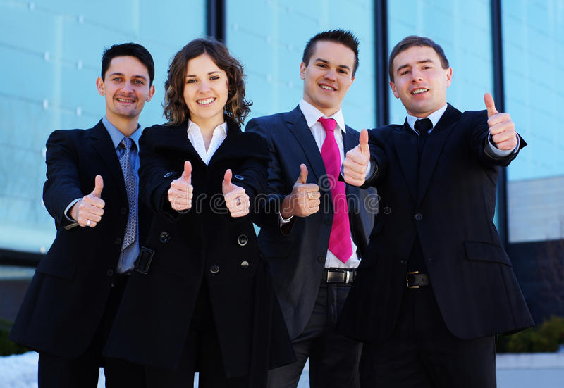 Four young business persons holding thumbs up stock images