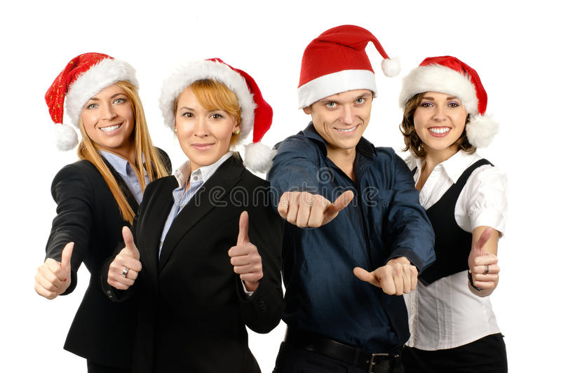 Four young businessperson in Christmas hats. Four young and happy businessperson in Christmas hats. The image is isolated on a white background royalty free stock images