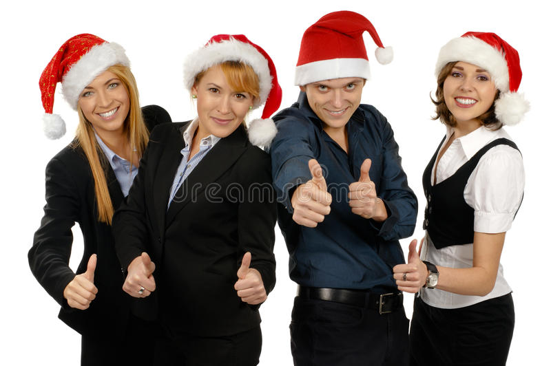 Four young businesspersons in Christmas hats. Four young and happy businesspersons in Christmas hats are holding thumbs up. The image is isolated on a white royalty free stock image