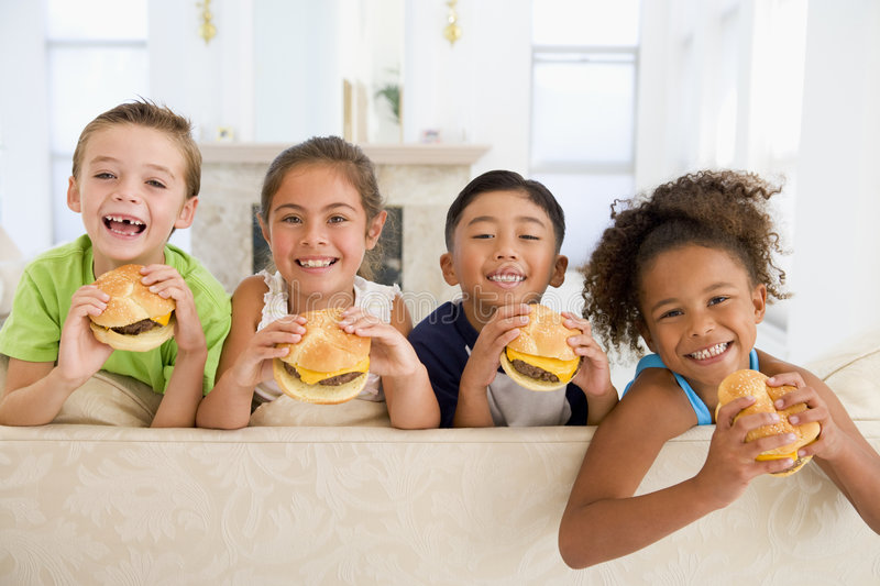 Four young children eating cheeseburgers stock photos