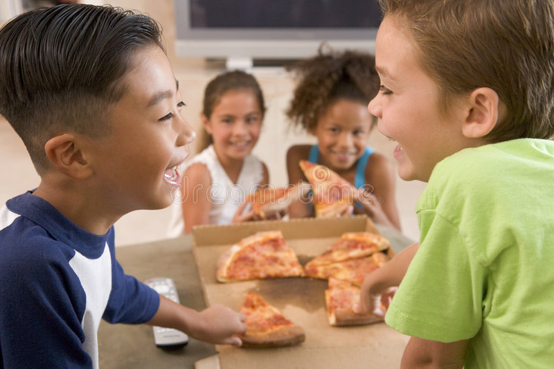 Four young children indoors eating pizza stock photo