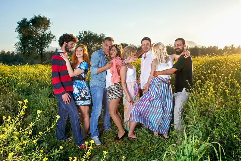 Four young couples enjoying a day in the country. Four young couples enjoying a day in the country grouped together standing in a colorful yellow rapeseed field stock photography