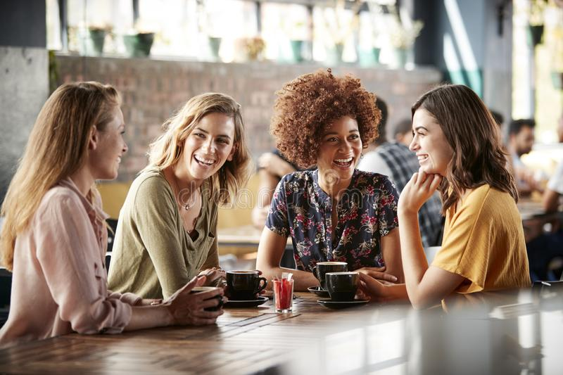 Four Young Female Friends Meeting Sit At Table In Coffee Shop And Talk stock photos