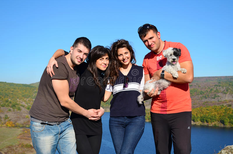 Four Young friends and dog hugging on a lake background royalty free stock photos