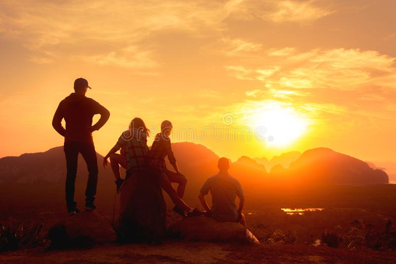 Four friends relax on sea and sunrise viewpoint stock photo