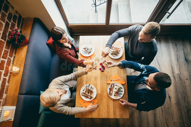 Four friends toasting in a restaurant. Top view. royalty free stock photos