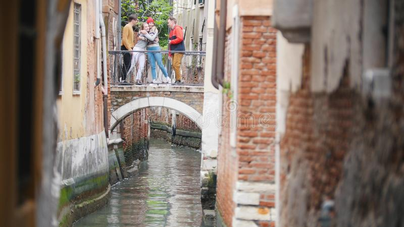 Four young friends standing on the bridge between two buildings above the water channel - two women hug - Venice, Italy royalty free stock image