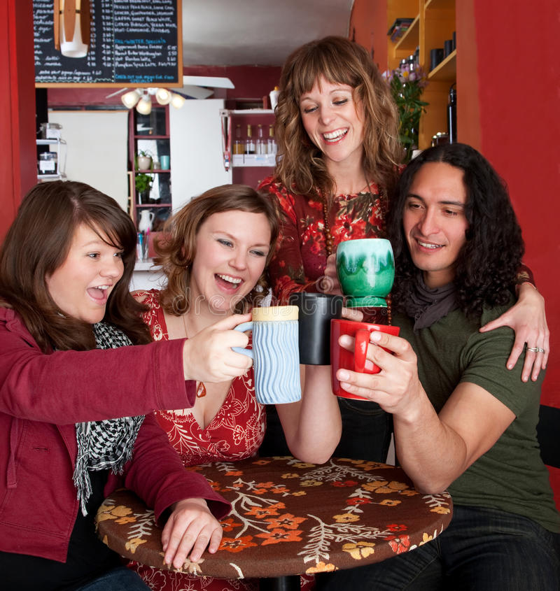 Four young friends toasting at a cafe stock image