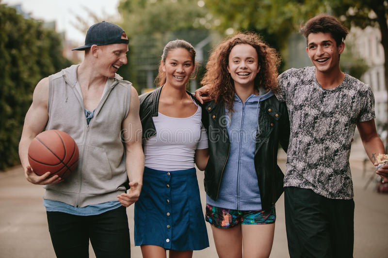 Four young friends walking together and smiling stock photo
