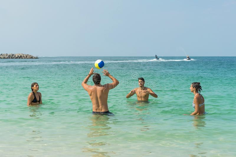 Four young fun people are playing volleyball on the beach at the coast of Dubai. Positive human emotions, feelings, joy. Funny cut royalty free stock photography