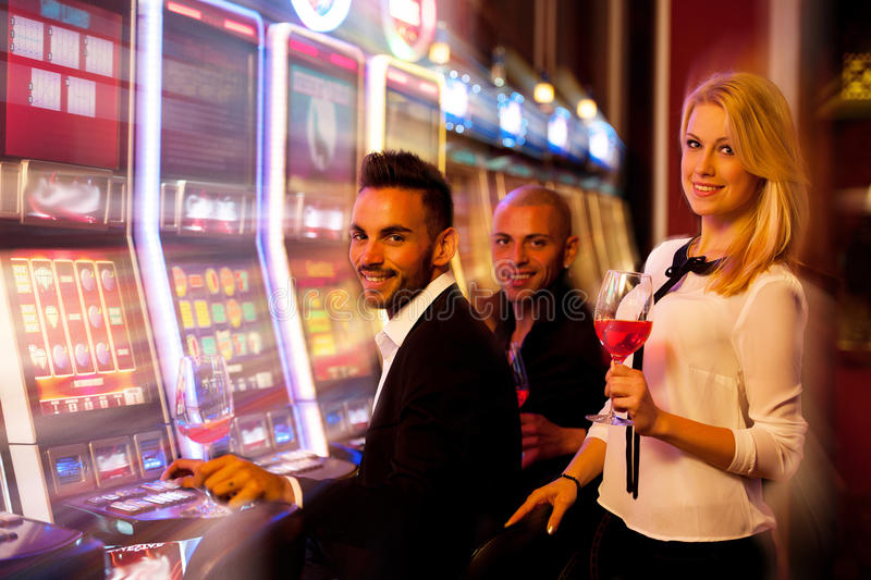 Four young people playing slot machines in casino stock images