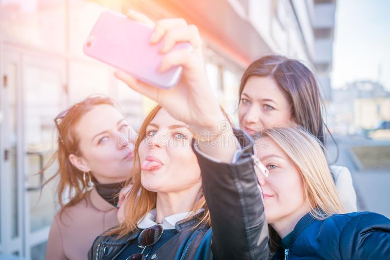 Four young very attractive women take selfies on urban streets stock photos