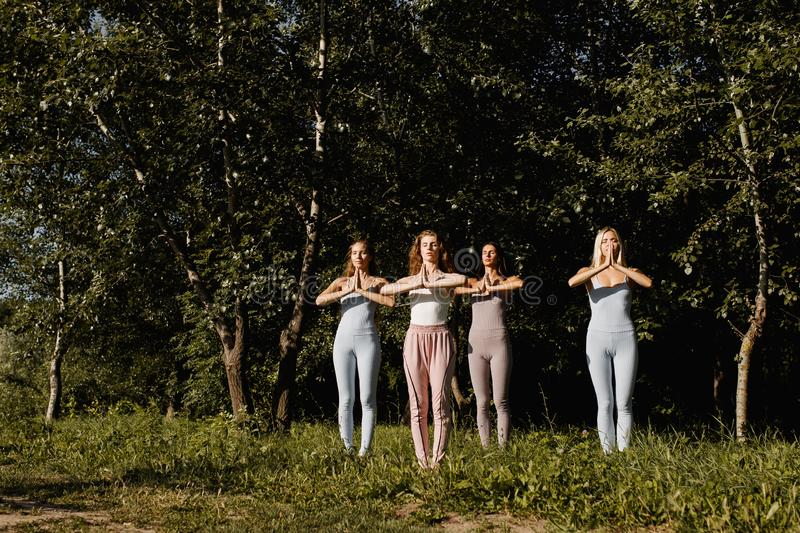 Four young women are practising yoga in the open air standing with folded hands near the chest in the nature on the. Grass royalty free stock photography