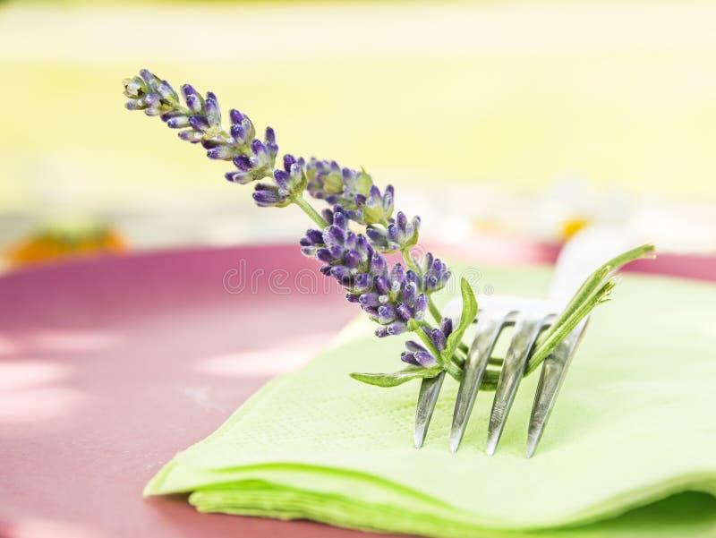Fourchette avec des fleurs de lavande sur la serviette verte photographie stock libre de droits