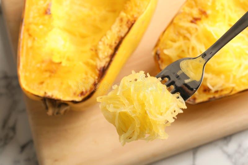 Fourchette avec la chair de la courge de spaghetti cuite sur le fond brouillé photographie stock