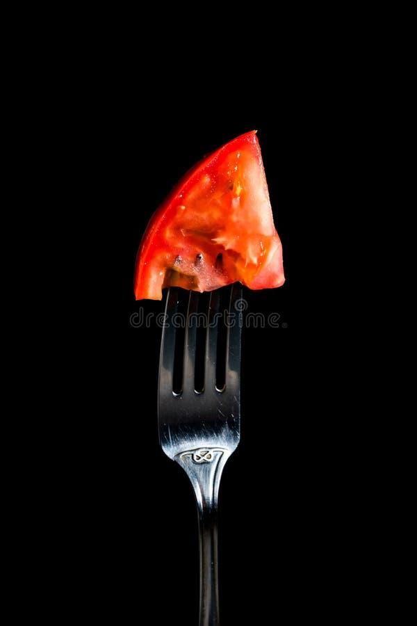 Fourchette avec une tomate inject?e sur un fond noir images libres de droits