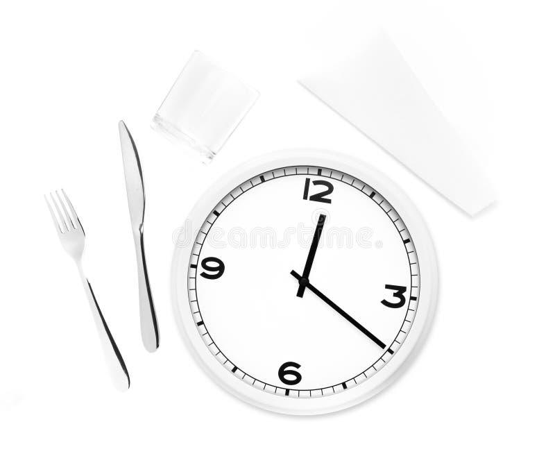 Fourchette, couteau, verre, serviette et horloge ronde blanche photo stock